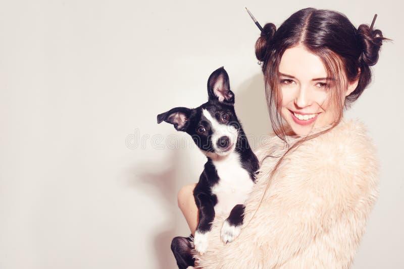 有小狗的愉快的女孩 妇女获得与她的狗的乐趣 获得狗的所有者与宠物的乐趣 在人和狗之间的友谊 宠物 图库摄影