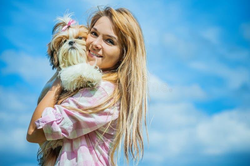 有小狗的美丽的微笑的少妇 免版税库存图片