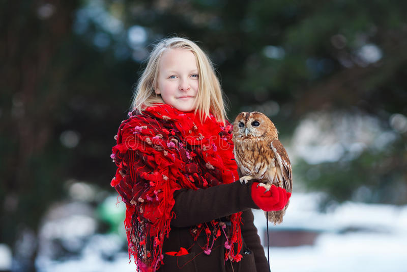 有小猫头鹰的逗人喜爱的女孩 免版税库存照片
