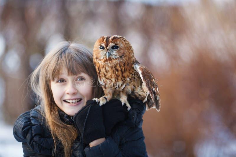 有小猫头鹰的逗人喜爱的女孩 免版税库存图片
