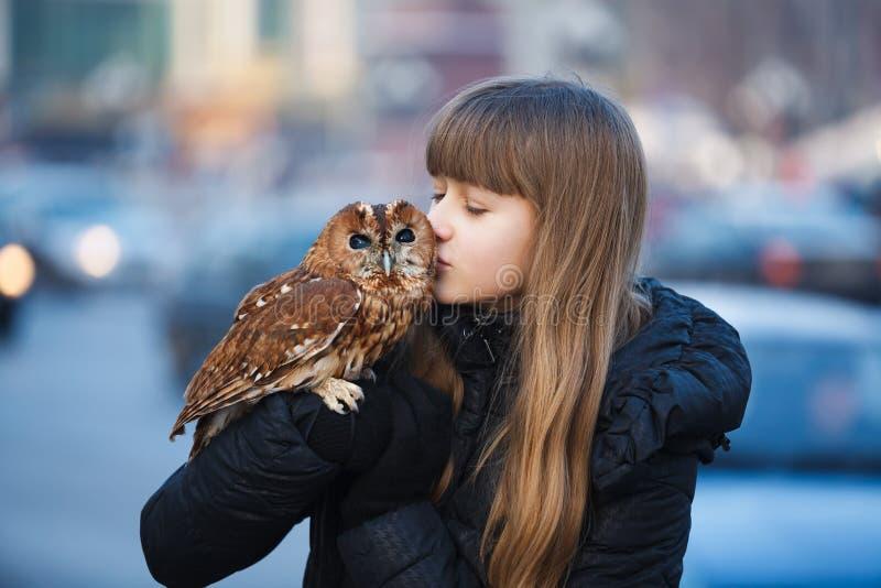 有小猫头鹰的逗人喜爱的女孩 免版税图库摄影