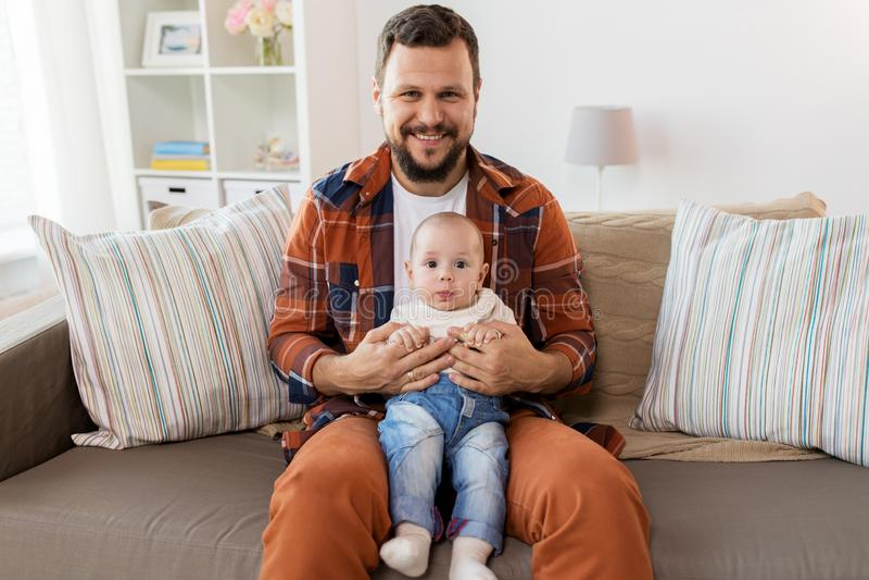 有小男婴的愉快的父亲在家 免版税图库摄影