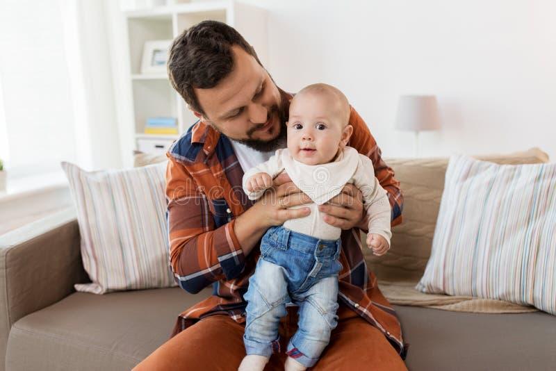 有小男婴的愉快的父亲在家 免版税库存照片