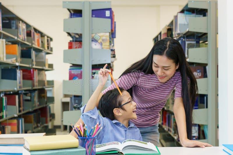有小男孩一起阅读书的美丽的妇女在图书馆里 库存照片