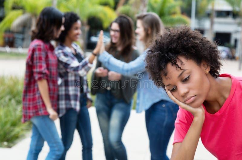 有小组的孤独的非裔美国人的妇女去其他女孩 免版税库存图片