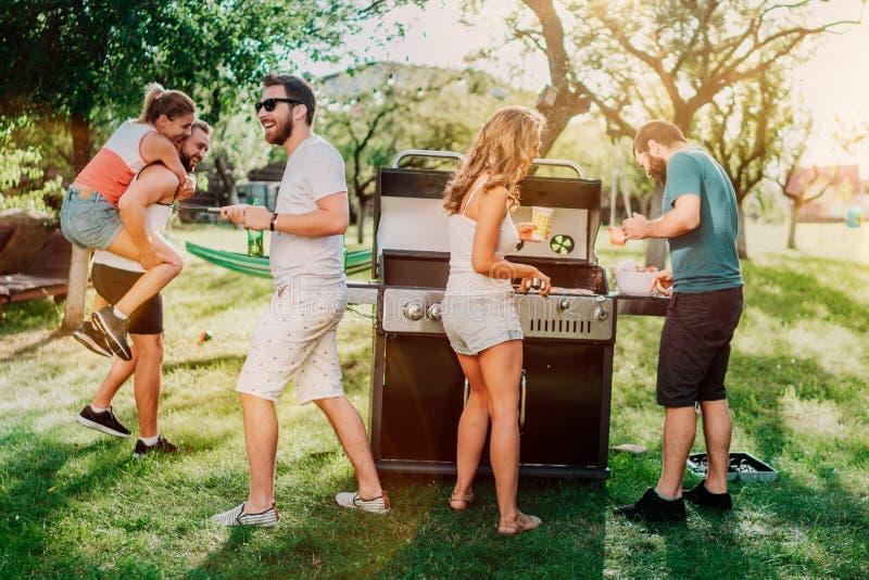 有小组的朋友一串室外庭院烤肉 有的人们美好时光,笑和微笑 免版税库存照片