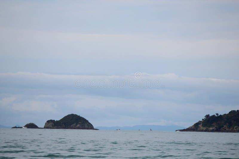 有小船和海岛的光滑的海 免版税库存照片