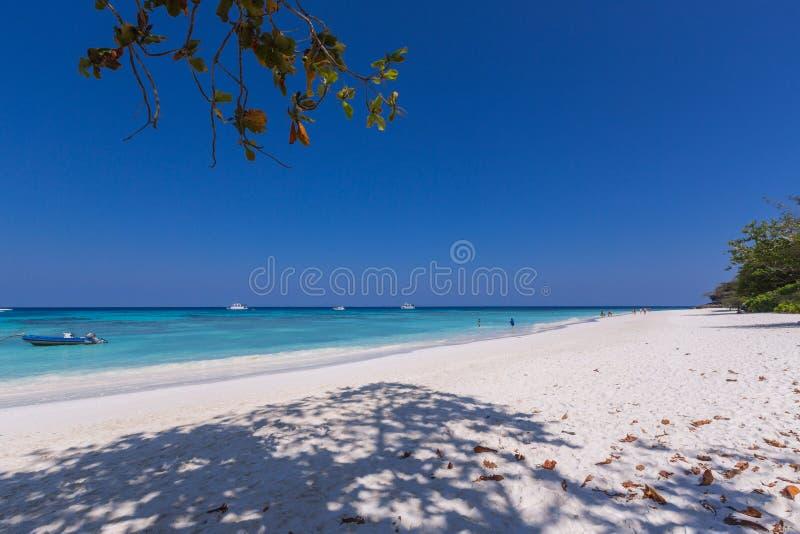 有小船和绿色山的美丽的海在背景 免版税库存图片