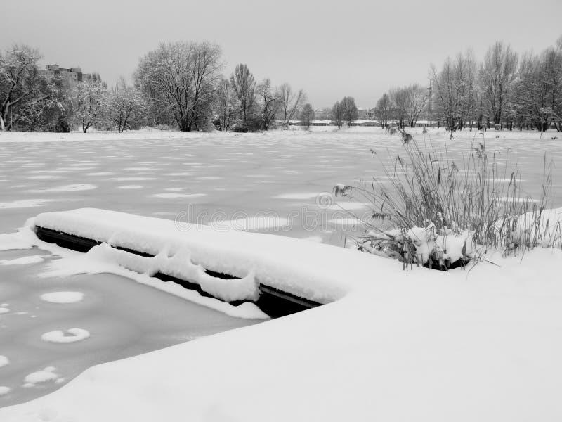 有小船港口的冻城市湖 免版税库存照片