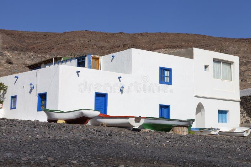 有小船的渔村白色房子在一个多岩石的海滩 免版税图库摄影