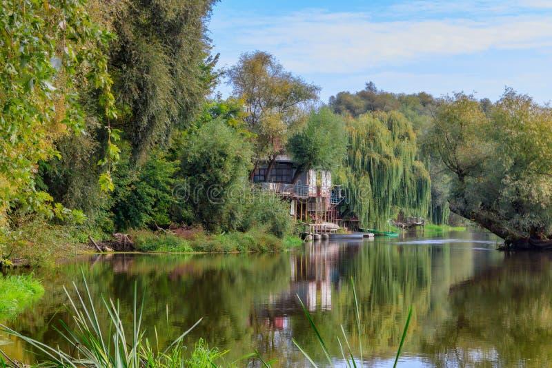 有小船的老木码头在反对绿色树的小河 河风景在晴朗的秋天早晨 免版税库存照片