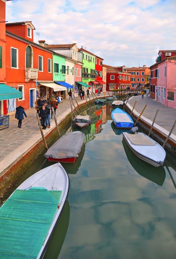 有小色的房子的行的,有fishermans小船的水运河,多云天空蔚蓝Burano海岛美丽如画的街道 免版税库存图片
