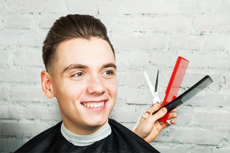 有小花卉纹发型的白年轻人在砖墙背景的理发店与梳子和剪刀 免版税库存照片