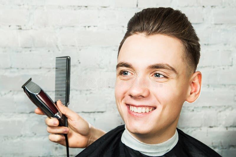 有小花卉纹发型的白年轻人在砖墙背景的理发店与梳子和剪刀 免版税库存图片