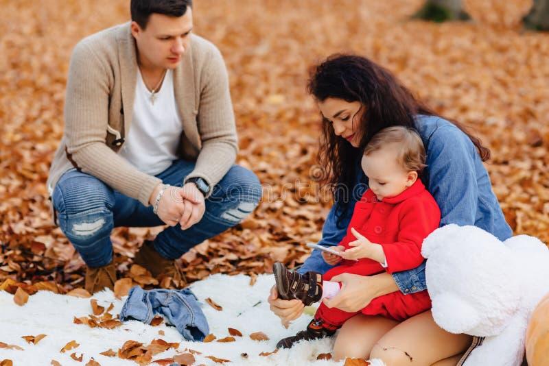 有小逗人喜爱的孩子的幸福家庭在黄色叶子的公园与 免版税库存图片