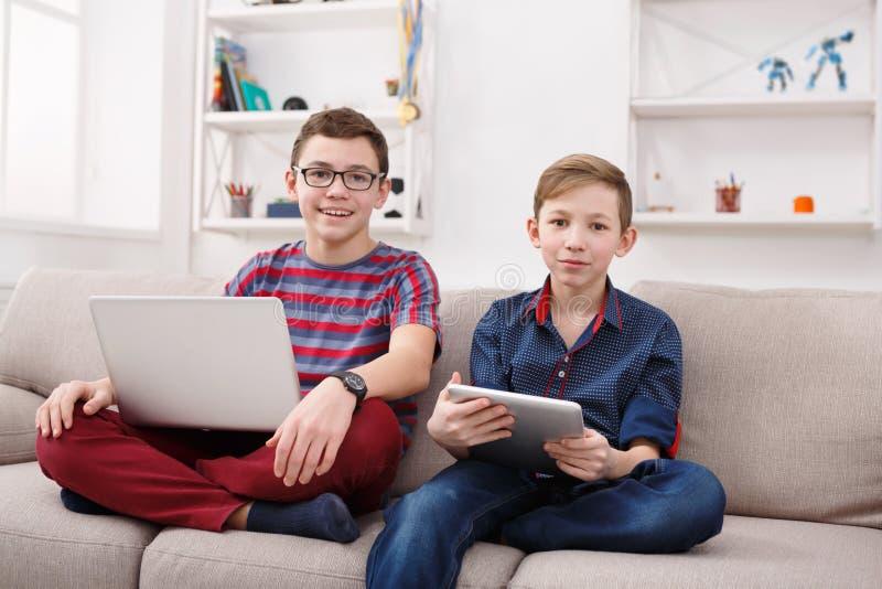 有小配件的两个十几岁的男孩在长沙发在家 免版税图库摄影