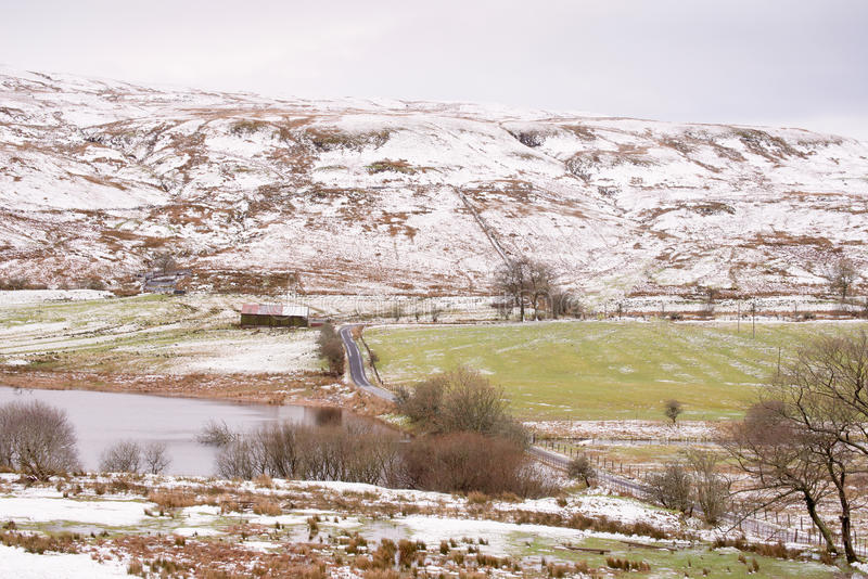 有小雪的冻冬天路在小山和海湾支持 免版税库存图片