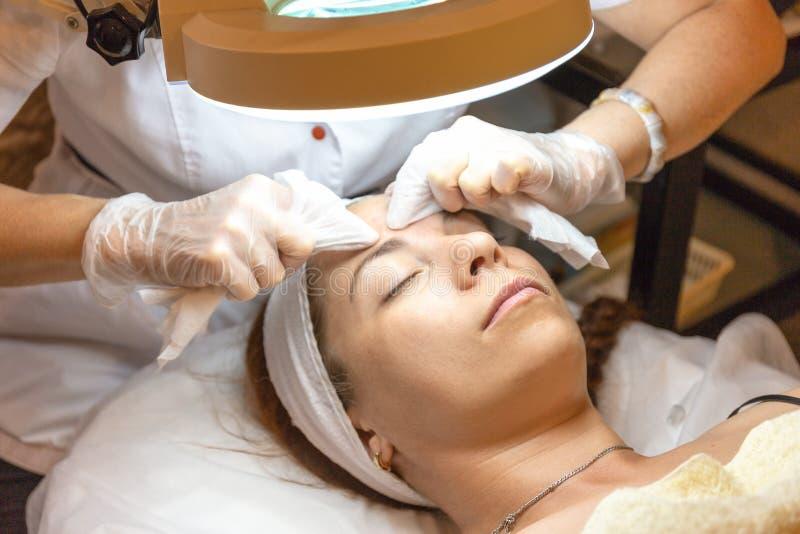 有少妇患者的美容师诊所的 面部皮肤回复的剥的和洗涤的做法,关闭  免版税库存照片