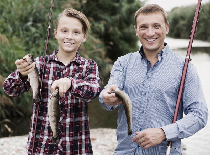 有少年男孩陈列抓住鱼的人 免版税库存照片