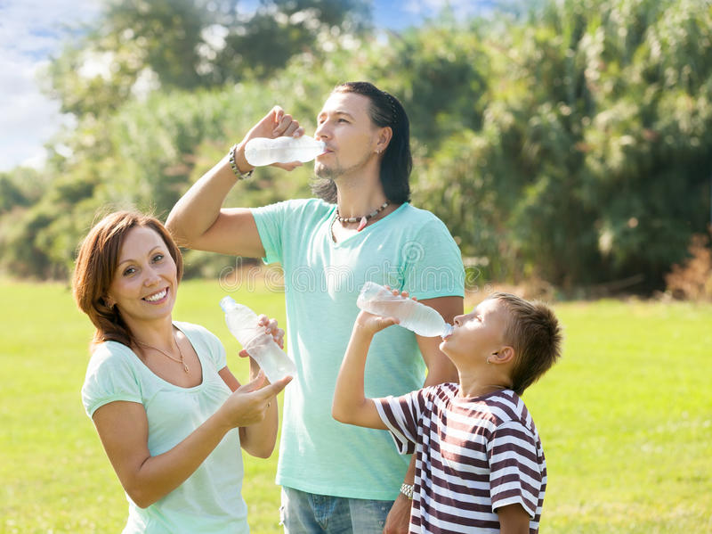 有少年饮用水的愉快的父母 图库摄影