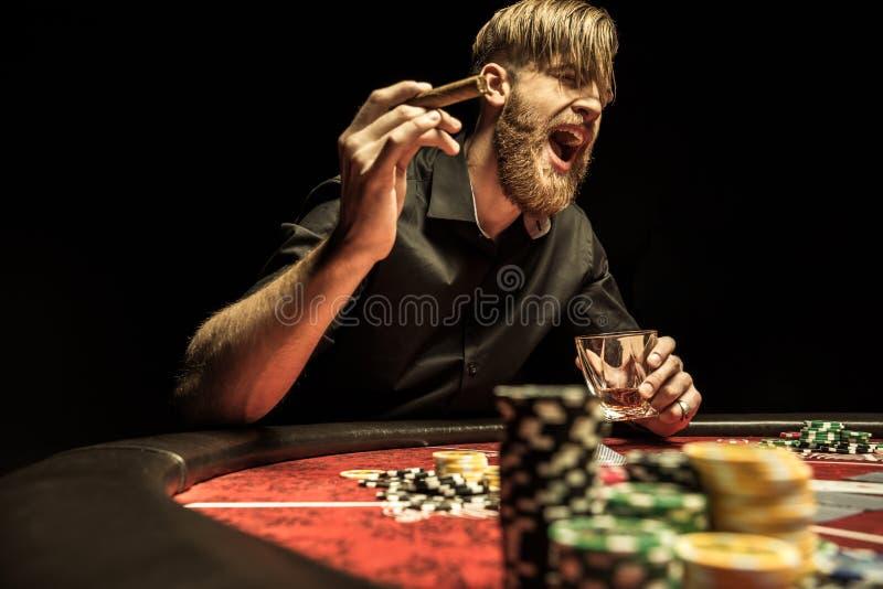 有尖叫的雪茄和的玻璃的人坐在啤牌桌上和 免版税图库摄影