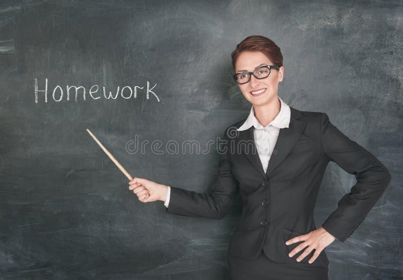 有尖和词组家庭作业的微笑的老师 库存图片