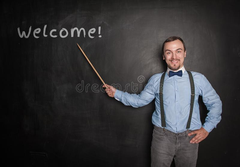 有尖的微笑的愉快的老师人在黑板 免版税库存照片