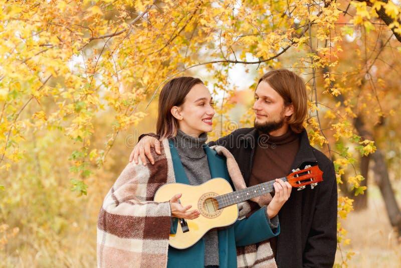 有尤克里里琴的一个女孩在她的手上看人在秋天背景旁边 图库摄影