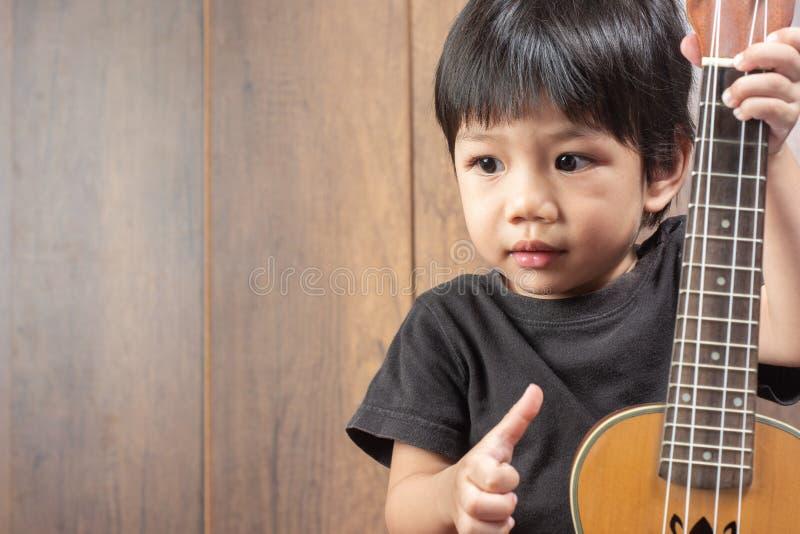 有尤克里里琴的逗人喜爱的矮小的亚裔男孩 图库摄影