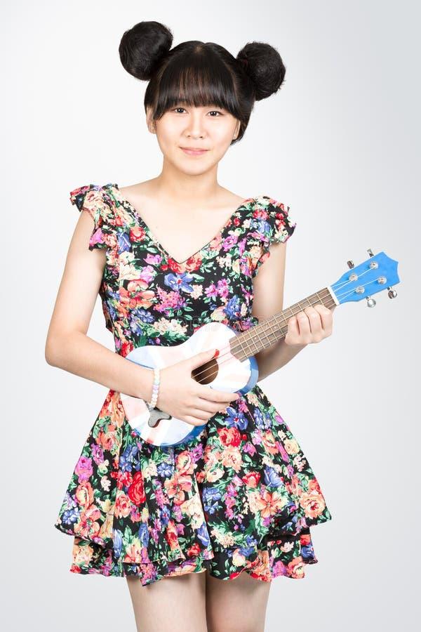 有尤克里里琴吉他的少年亚裔女孩 免版税库存照片