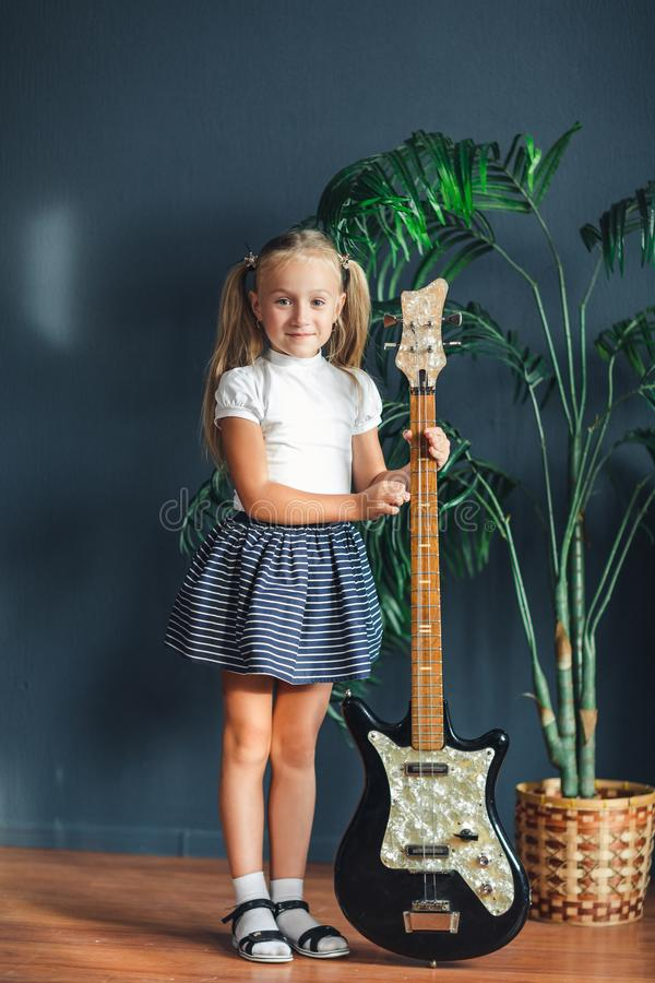 有尾巴的年轻白肤金发的女孩在白色T恤、裙子和凉鞋与在家看照相机和微笑的电吉他 免版税库存图片