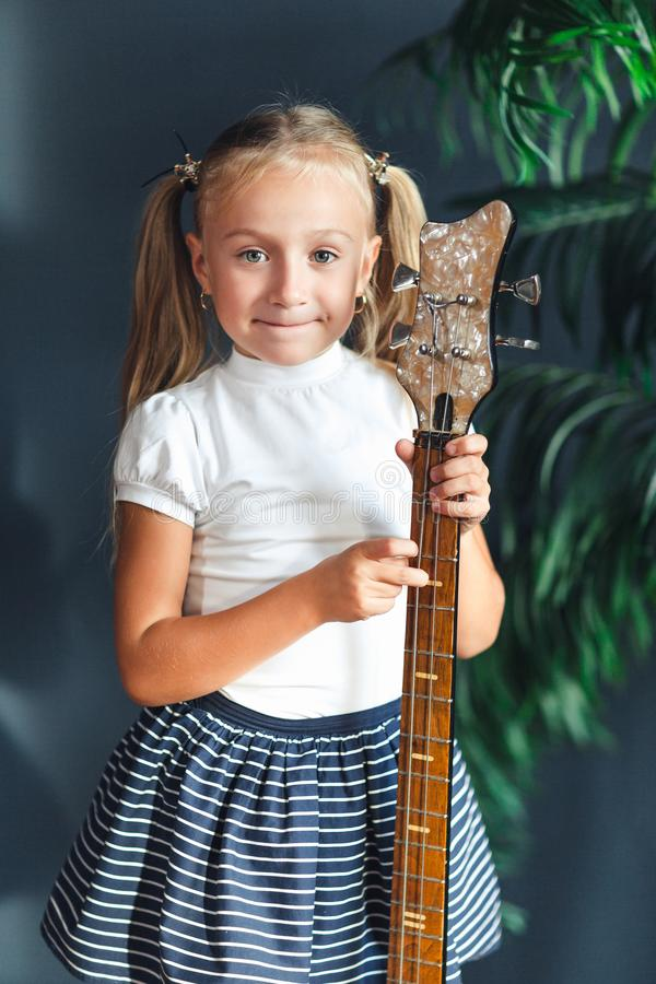 有尾巴的年轻白肤金发的女孩在白色T恤、裙子和凉鞋与在家看照相机和微笑的电吉他 免版税库存照片