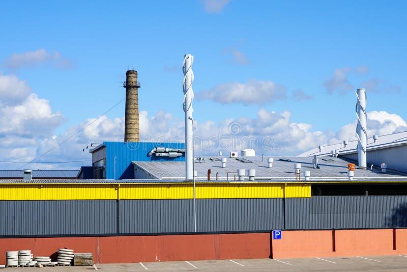 有尾气和透气烟囱的现代工厂厂房墙壁和屋顶 图库摄影