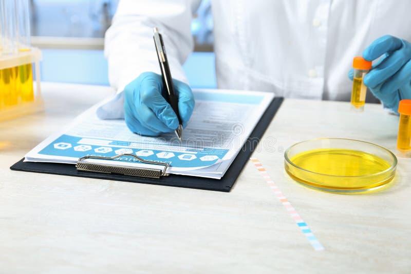 有尿样的实验员分析的写测试的结果在桌上户内 库存照片
