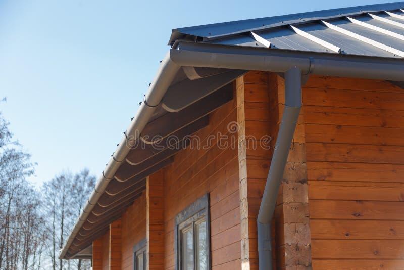 有屋顶排水系统的木木屋 免版税库存图片