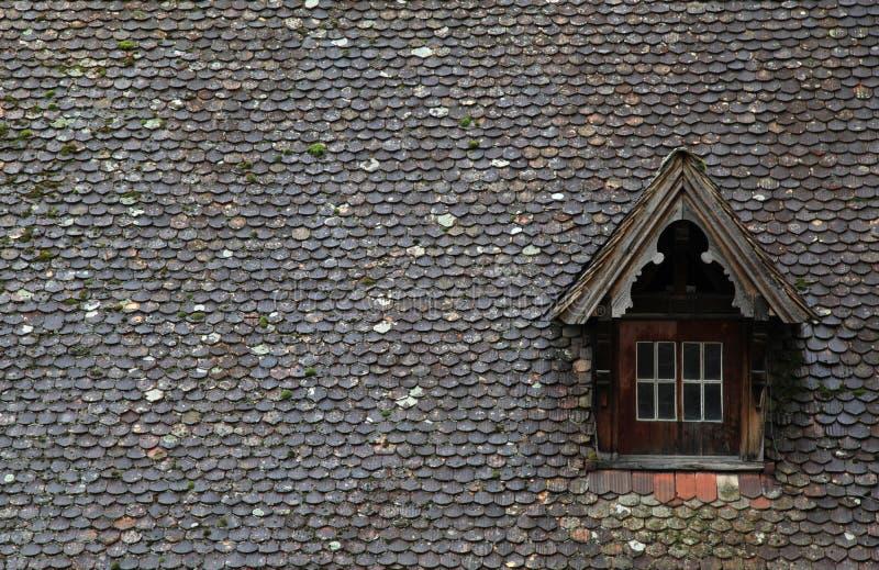 有屋顶窗的老棕色瓦屋顶 图库摄影