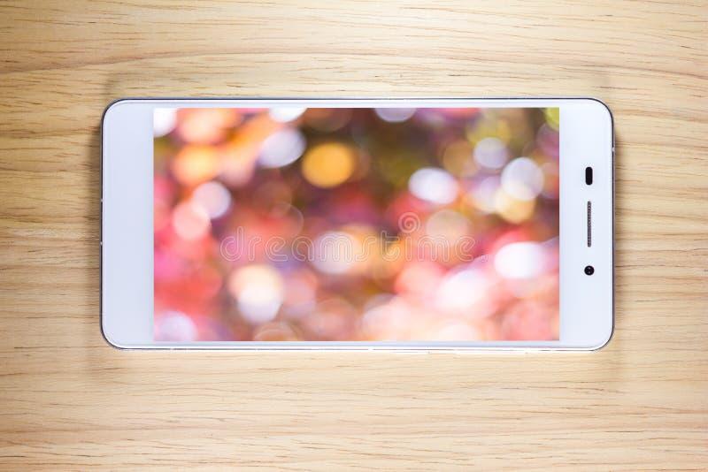 有屏幕的白色巧妙的电话在木背景 免版税库存图片