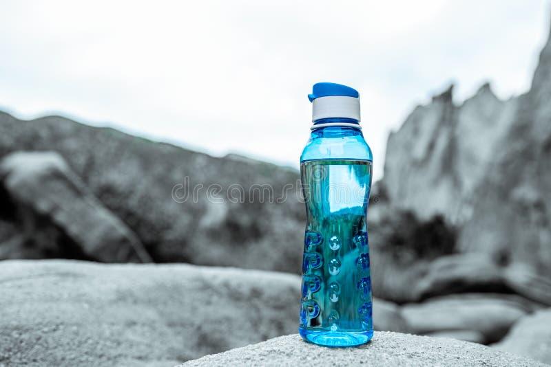 有山的水色蓝色健身水瓶在背景中 库存图片