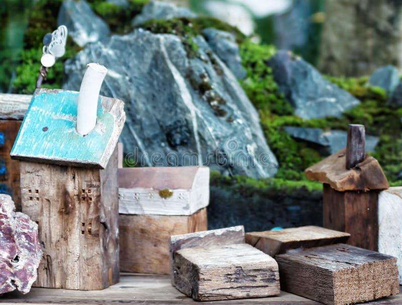 有岩石和青苔的玩具木房子 免版税库存照片