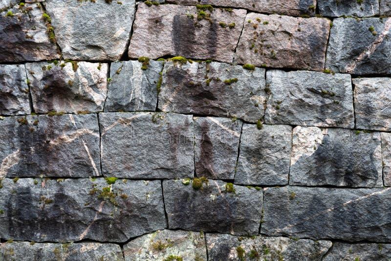 有岩石整洁地适合的坚实块的老手工制造岩石墙壁  免版税图库摄影