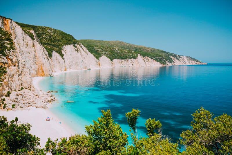 有岩石海岸线的, Kefalonia,希腊晴朗的Fteri海滩盐水湖 在伞冷颤下的游人在清楚的蓝色附近放松 库存照片