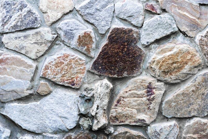 有岩石的另外大小的自然石墙 土气石表面饰板在树荫下棕色和米黄;与自然sto的墙壁覆盖 图库摄影