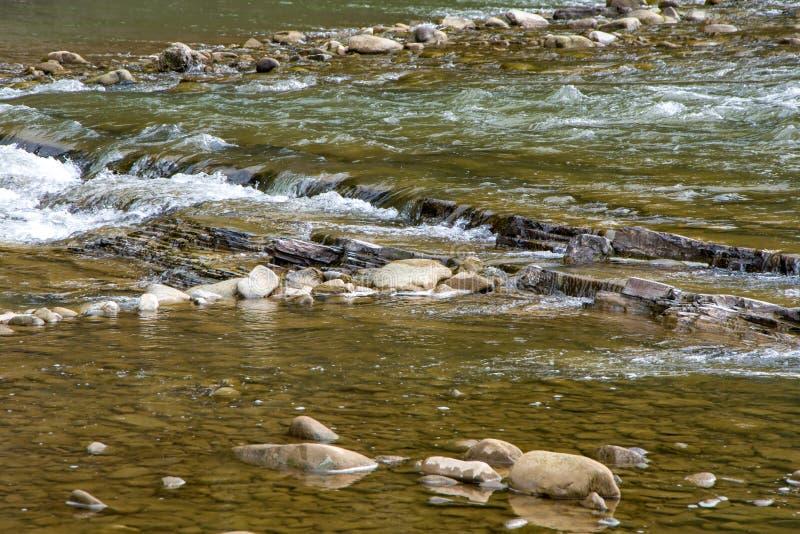有岩石裂口的山从山的河,水流量,旅游业和旅行 库存图片