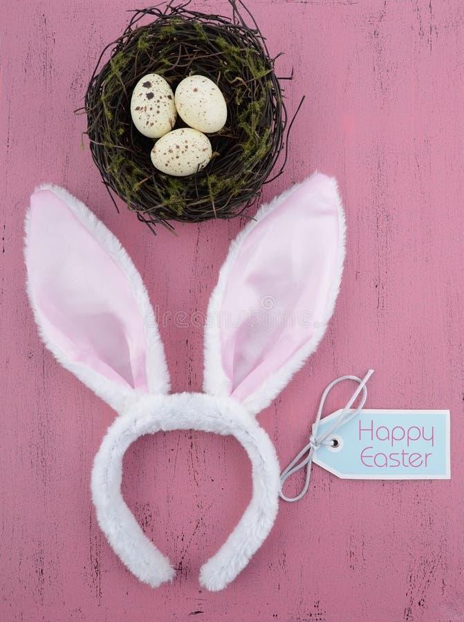 有巢的愉快的复活节兔子耳朵在桃红色木头-垂直 免版税图库摄影