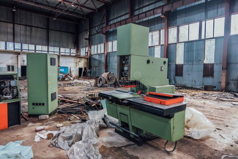 有工业计算机数控机床生锈的遗骸的老被放弃的金属工艺工厂在车间 免版税库存照片