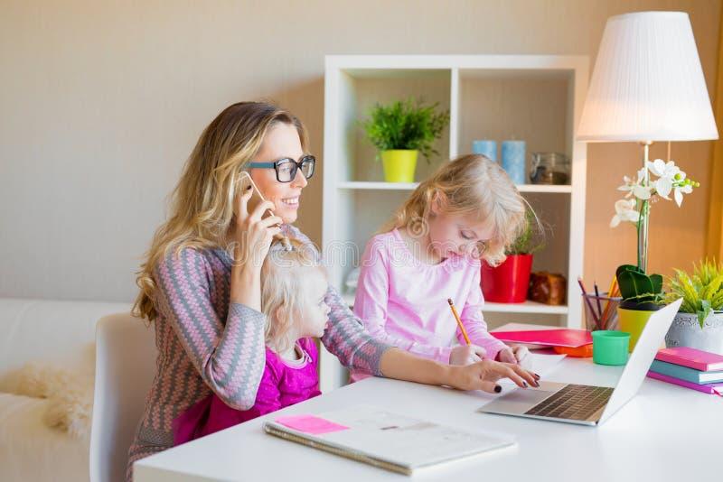 有工作从家的两个女儿的妈妈 库存图片