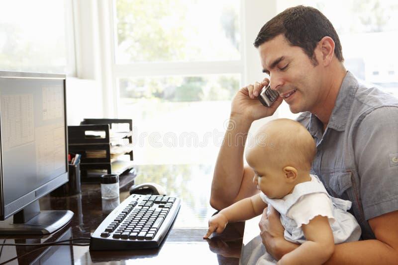 有工作在家庭办公室的婴孩的西班牙父亲 库存照片