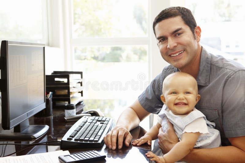 有工作在家庭办公室的婴孩的西班牙父亲 免版税库存照片