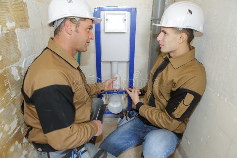 有工作的经理的年轻水管工户内 免版税库存图片
