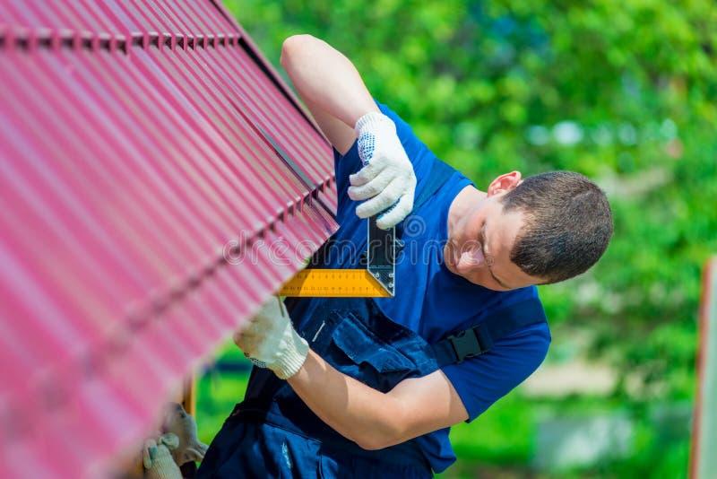 有工具的杂物工在屋顶的修理期间 免版税库存照片